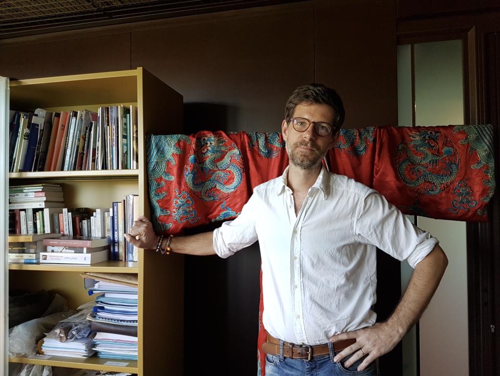 Philippe Charlier dans son bureau du musée du quai Branly - Jacques Chirac (à l'arrière-plan, un costume d'exorcisme taoïste de la fin du 19e siècle) ©UVSQ